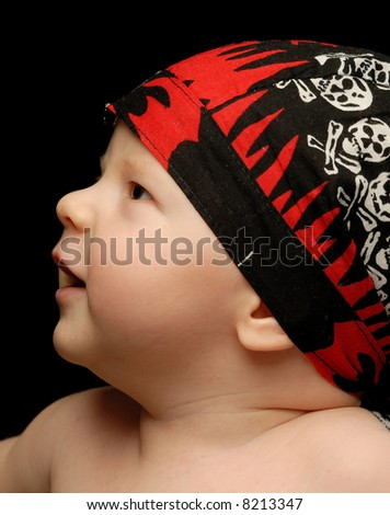 Close-up portrait of a little baby in sculled bandanna looking up - stock photo