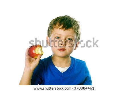 Close-up portrait of a little boy eating red apple isolated on white background - stock photo