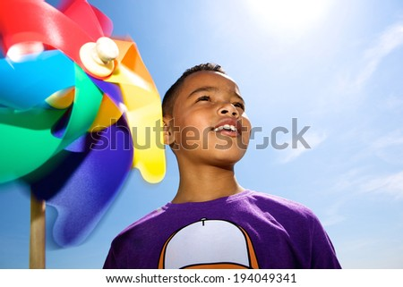Close up portrait of a little boy smiling outdoors with colorful windmill - stock photo