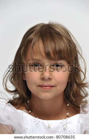 Close-up portrait of a little girl dressed up in a white pretty dress - stock photo