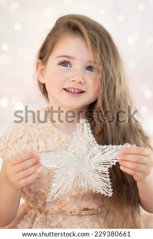 Close-up portrait of a little girl on Christmas day with a star in hands. Preparing for Christmas. - stock photo