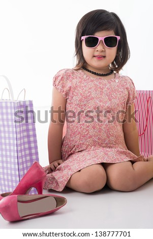 Close-up portrait of a little girl sitting on the floor in the sun-glasses - stock photo