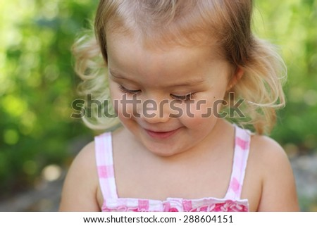 Close up portrait of a little smiling happy girl in a sunny summer day on green background