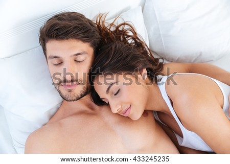 Close-up portrait of a lovely beautiful couple sleeping in bed at home - stock photo