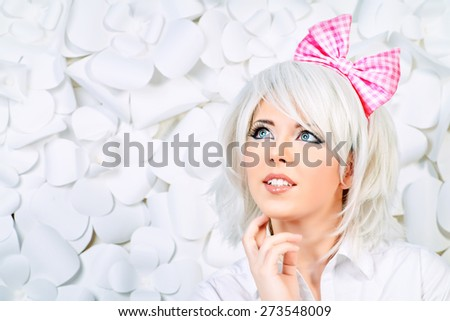 Close-up portrait of a lovely girl wearing white wig and white blouse posing over  background with paper flowers. Anime style.  - stock photo
