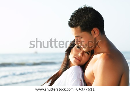 close up portrait of a  loving couple looking at the horizon from the shore of the beach - stock photo