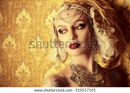 Close-up portrait of a magnificent traditional female dancer over golden vintage background. Ethnic dance. Belly dancing. Tribal dancing. Make-up, cosmetics. - stock photo