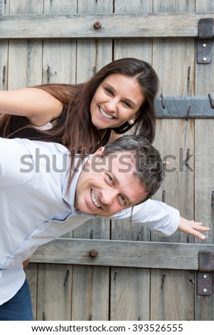 Close up portrait of a  man giving piggyback to woman on the beach.