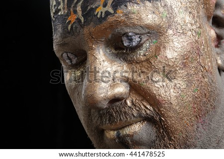 close-up portrait of a man in the clay body art , studio on a dark background
