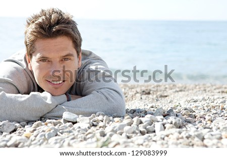 Close up portrait of a man laying down on the shore of a white pebble beach smiling with the blue sea in the background. - stock photo