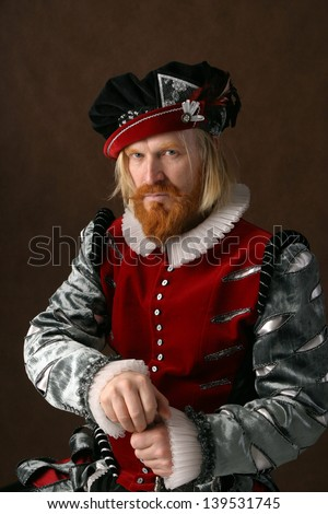 close-up portrait of a man of the Middle Ages with a beard and mustache in a suit isolated on a dark background - stock photo