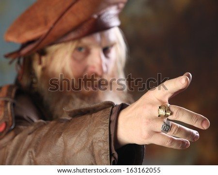 Close-up portrait of a man with a beard and mustache in a leather coat and beret out of focus in the foreground hand with rings on his fingers, stretching to the camera, studio