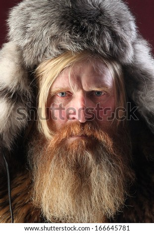 close-up portrait of a man with a long beard and mustache, wearing a fur hat, studio shot on a burgundy background - stock photo