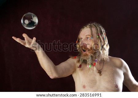 close-up portrait of a man with a long beard, mustache and hair braided in pigtails plays with glass sphere studio on dark background - stock photo