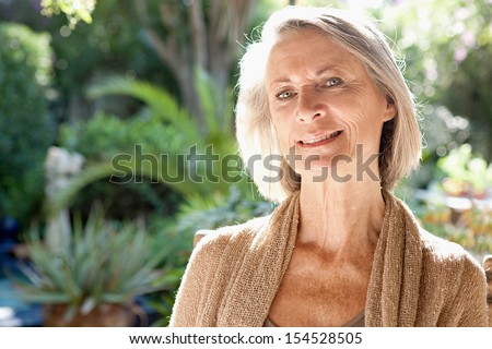 Close up portrait of a mature attractive woman sitting and relaxing in a home garden during a bright and golden summer sunny day, smiling outdoors. - stock photo