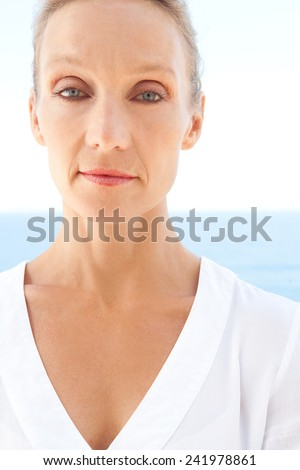 Close up portrait of a mature beautiful blond caucasian woman standing against a blue sea and sky with a confident, strong and proud expression. Healthy lifestyle, wellness and care outdoors. - stock photo