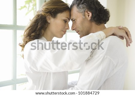 Close up portrait of a mature couple hugging and holding their foreheads together, in a romantic moment at home.