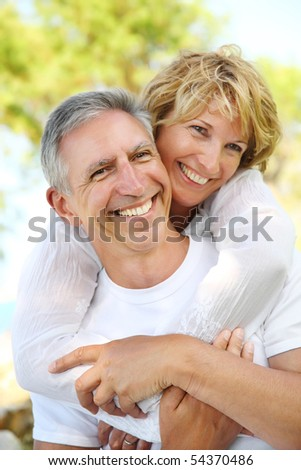 Close-up portrait of a mature couple smiling and embracing. Focus on the man.