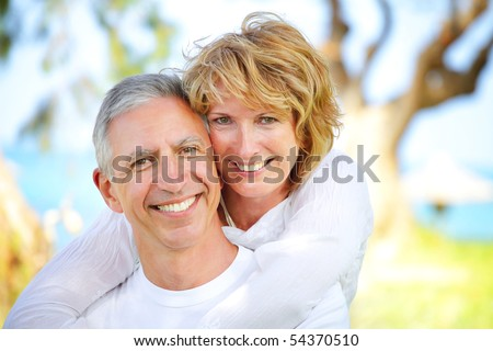 Close-up portrait of a mature couple smiling and embracing. Focus on the woman. - stock photo