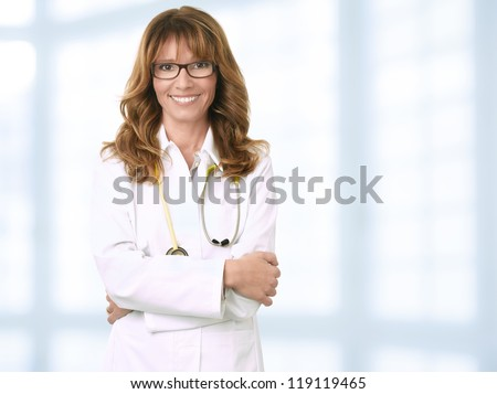 Close-up portrait of a mature female doctor smiling - stock photo