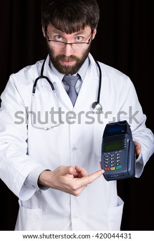 close-up portrait of a medical doctor, he proposes to pay for treatment in pos-terminal. concept of high cost of the treatment  - stock photo