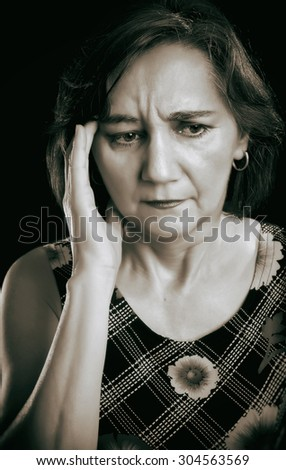 Close-up portrait of a middle aged woman with headache, massaging forehead with her right hand. Sepia picture, isolated on black. - stock photo