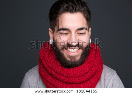 Close up portrait of a modern young man with beard and piercings smiling on gray background - stock photo