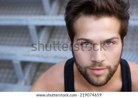 Close up portrait of a modern young man with beard staring  - stock photo