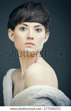 Close up portrait of a modern young woman looking at camera. Short pixie hair & body piercings