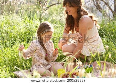 Close up portrait of a mother and daughter relaxing together having a picnic in a lush green garden eating healthy food, smiling having fun. Family activities and healthy eating lifestyle, outdoors. - stock photo
