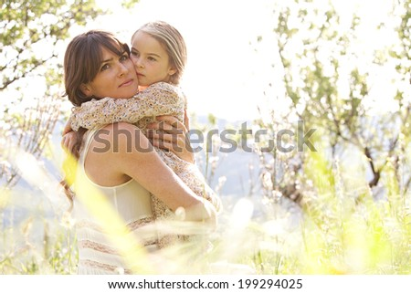 Close up portrait of a mother and daughter relaxing together in a beautiful spring field of grass and flowers, hugging and enjoying a sunny holiday outdoors. Family love holiday activities lifestyle. - stock photo