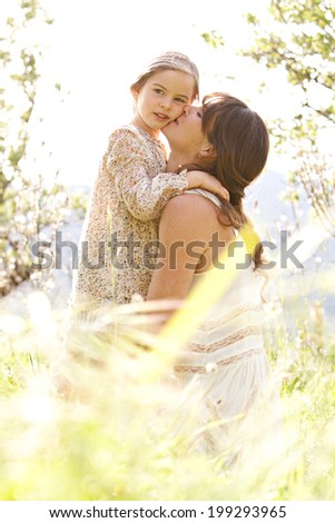 Close up portrait of a mother and young daughter hugging in a beautiful spring field of green grass and flowers, enjoying a sunny holiday outdoors. Family love and holiday activities lifestyle. - stock photo