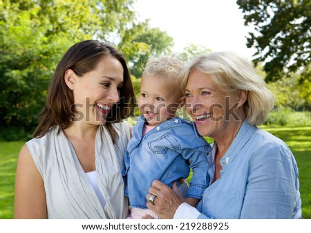 Close up portrait of a mother smiling with baby and grandmother - stock photo