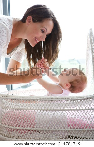 Close up portrait of a mother smiling with infant child in bed - stock photo