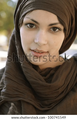 Close up portrait of a muslim woman wearing a head scarf and looking at camera. - stock photo