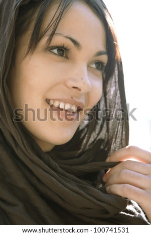 Close up portrait of a muslim woman wearing a head scarf, smiling. - stock photo