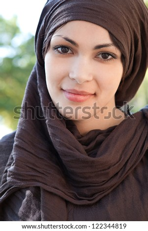 Close up portrait of a muslim young woman wearing a head scarf and smiling at the camera, outdoors. - stock photo