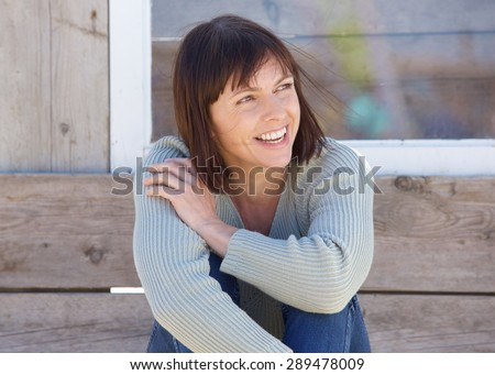 Close up portrait of a natural older lady smiling outside - stock photo