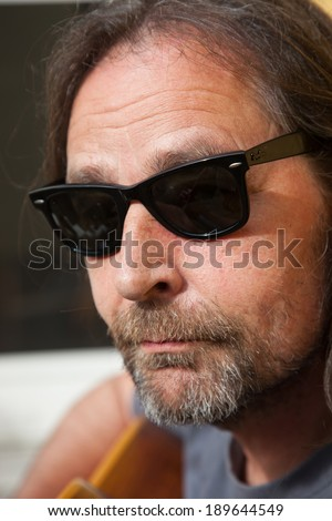 Close-up portrait of a nonconformist Caucasian middle-aged bearded man looking at camera through trendy dark black plastic sunglasses - stock photo