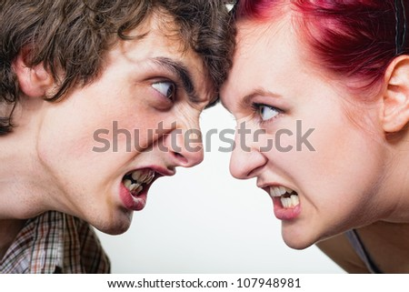 Close-up portrait of a pair of angry shouting against each other on a white background - stock photo