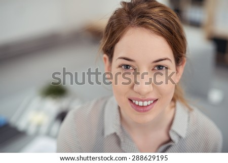 Close up Portrait of a Pretty Blond Teen Girl Looking at the Camera from High Angle View, with a Toothy Smile.