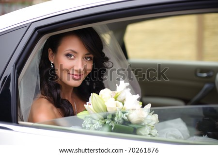 close-up portrait of a pretty bride in a car window - stock photo