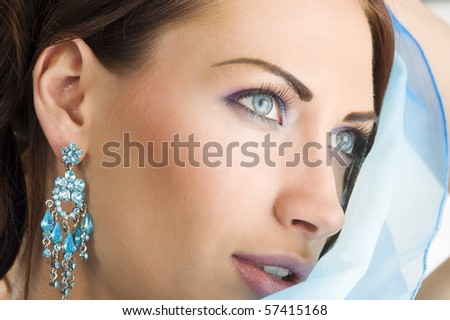 close up portrait of a pretty brunette with blue-sky earring playing to hide her face with a summer headscarf - stock photo