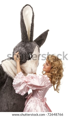 Close-up portrait of a pretty girl in pink dress with a big grey fur's color rabbit against white background - stock photo