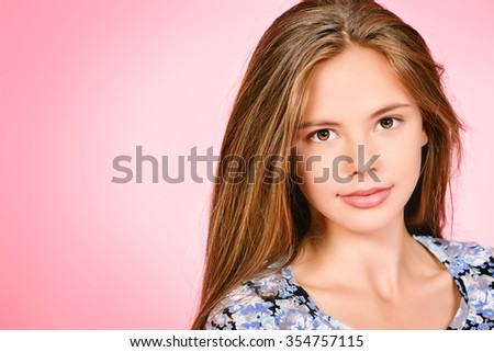 Close-up portrait of a pretty girl teenager with beautiful healthy long hair over pink background. Studio shot. - stock photo