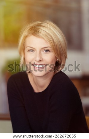 Close up Portrait of a Pretty Smiling Woman with Short Blond Hair, Wearing a Casual Black Shirt, Looking at the Camera.