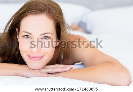 Close-up portrait of a pretty smiling young woman lying in bed at home - stock photo