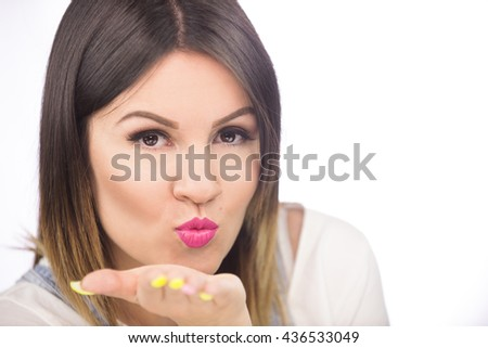 Close up portrait of a pretty teenage brunette girl posing blowing a kiss smiling - stock photo