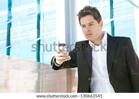 "Close up portrait of a professional business man holding a ""smart phone"" and dialing while leaning on the glass banister of a modern office building in the city. - stock photo"