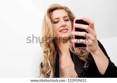Close up portrait of a professional woman holding and using a smart phone in her hand against a white background.